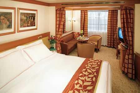 Suite Deluxe Sabord : Un grand lit, espace salon, mini-bar, TV magnétoscope, salle de bains en marbre. Superficie de la cabine : 28 m²
